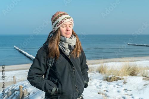 glückliche Frau am Meer im Winter mit geschlossenen Augen