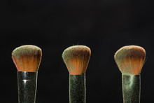 Make Up, Beauty And Mineral Powder Concept - Three Dirty Brushes Over The Black Background
