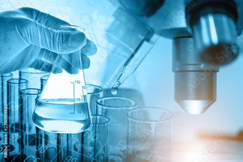 Flask in scientist hand with microscope and lab glassware background