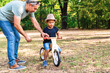 Father teaching his son to ride wooden bike in park