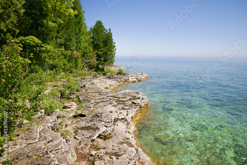 Foto op Plexiglas Cyprus Bright blue ake to the right, gray rocky terrain with green trees on the left in Peninsula State Park in Door County Wisconsin