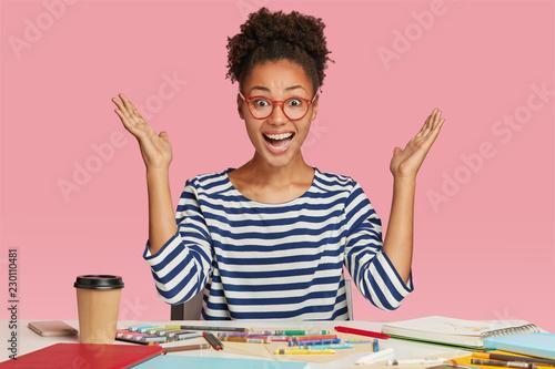Amazed black female illustrator raises hands in eureka gesture
