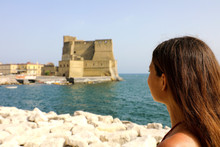 Rear View Of Beautiful Woman Looking To Egg Castle (Castle Dell'Ovo) A Medieval Fortress In The Bay Of Naples, Italy