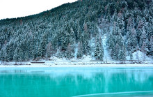 The Frozen Turquoise Lake And The Snow-covered Forest