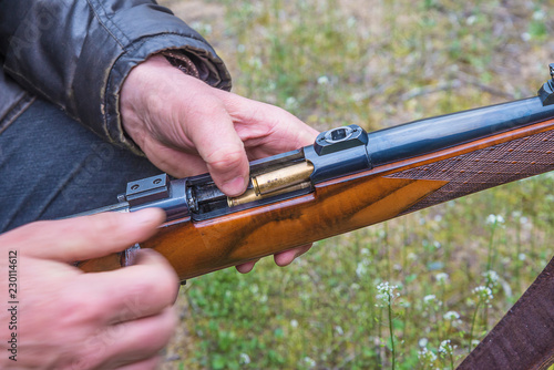Men's hands loading the hunting carbine with bullet close up