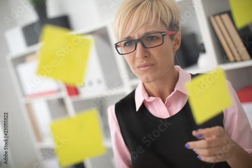 Fototapety, obrazy: A young girl stands in the office near a transparent Board with stickers and reads what is written on them.