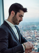 Portrait Of Stylish Young Man Wearing Business Suit, Standing In Modern City Setting, Looking At Wrist Watch To Check The Time