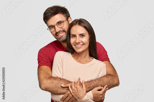 Fotografía Lovely couple have warm cuddle, pose for family portrait, smile joyfully, have good relationships