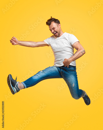 Valokuva  Man jumping and pretending to play guitar