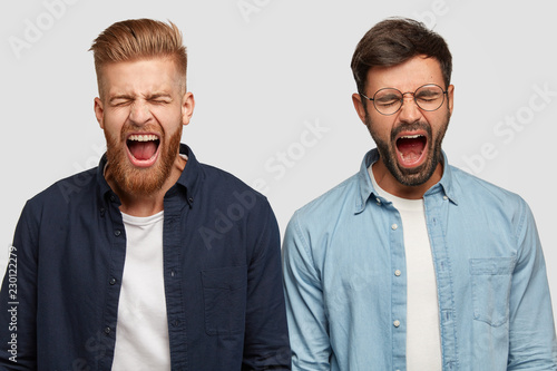 Photo of annoyed guys produce loud yell, open mouth widely, have trendy haircut and bristle, stand shoulder to shoulder against white background Fototapete