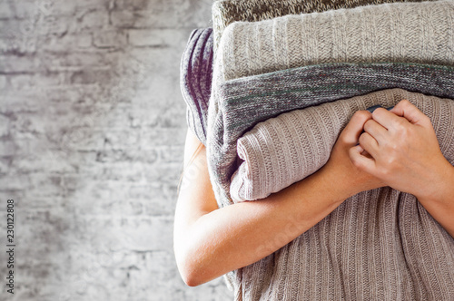 Fotografiet  woman holding in hands Stack of cozy knitted sweaters on gray wall background