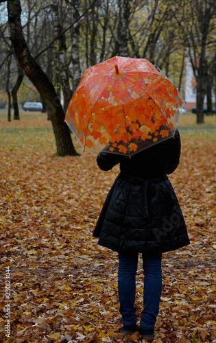 Девушка в чёрном пальто с ярким зонтом со спины