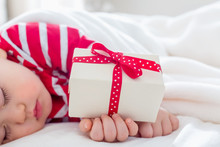 Toddler Boy Sleeping In His House With A Christmas Gift