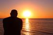 Leinwandbild Motiv An elderly man sits by the sea and watches the sunset. Background. Landscape.