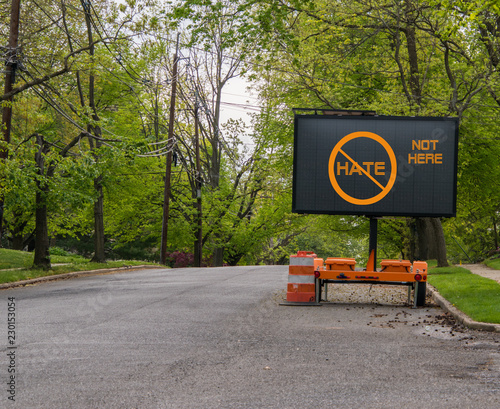 Fotografia, Obraz  Electric traffic street sign on quiet neighborhood street that says no hate, not here