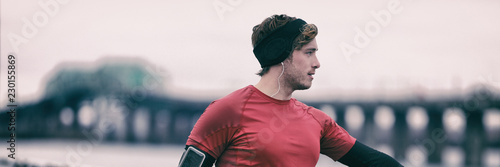 Poster Glisse hiver Winter runner man in cold outdoor air training cardio. Male runner stretching after running in fall weather wearing warm sport running clothing. Handsome male fitness sport model outdoors. Panoramic.