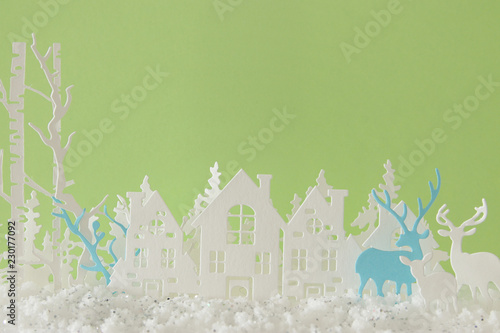 Poster Muguet de mai Magical Christmas paper cut winter background landscape with houses, trees, deer and snow in front of pastel green background.