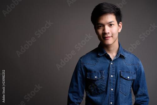 Foto  Young handsome Asian man wearing denim shirt