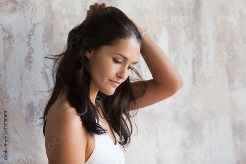 Photo  Young brunette woman shyly smiles and looks down