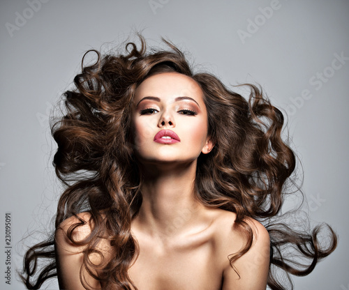Face of a beautiful  woman with long flying   hair Fotobehang