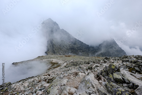 Tuinposter Grijs peak of Rysy mountain covered in mist. autumn ascent on hiking trails