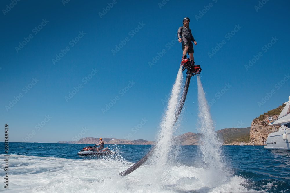 Fototapety, obrazy: Flyboarding and seariding on the Sea near the mountain island. Water summer extreme sports.