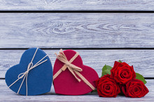 Two Heart-shaped Gift Boxes And Flowers. Blue And Red Gift Boxes In A Shape Of Heart With Red Roses On Gray Wooden Background. Love And Romance Concept.