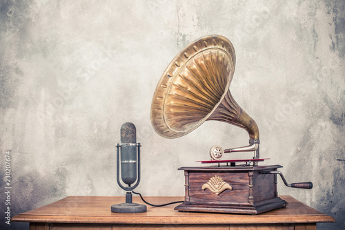 Vintage antique gramophone phonograph turntable with brass horn and big aged studio microphone on wooden table front concrete wall background Canvas Print