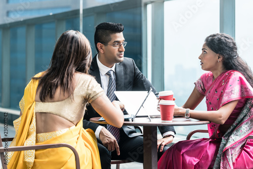Fotografía  Three Indian business people with worried facial expression talking during break
