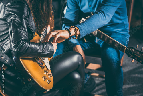 Guitar music teacher helping his student to play, closeup on the hands - 230211250