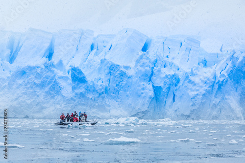 Fotobehang Antarctica Snowfall over boat with tourists in the bay full of icebergs with huge glacier wall in the background, near Almirante Brown, Antarctic peninsula