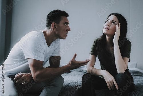 Photo Married Couple Sitting on Gray Bed and Arguing