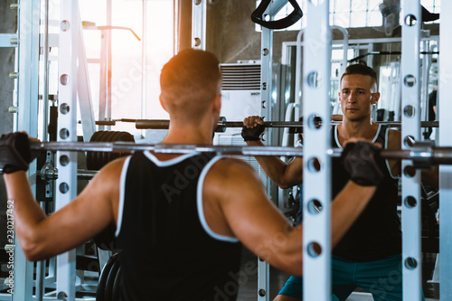 Foto op Plexiglas Fitness A Handsome man squats in a gym, view on the reflection in the mirror