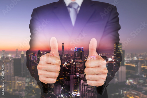 Fotomural Double exposure of businessman give a two thumbs up for compliment and cityscape