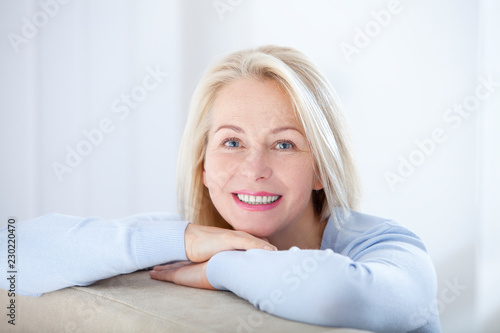 Active beautiful middle-aged woman smiling friendly and looking in camera Tableau sur Toile