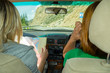 Two young woman travelling by car one in the passenger seat looks at the paper map looking for the desired route and indicates the road while traveling through the mountains of the Altai