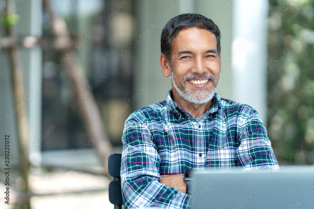 Fototapeta Portrait of happy mature man with white, grey stylish short beard looking at camera outdoor. Casual lifestyle of retired hispanic people or adult asian man smile with confident at coffee shop cafe.