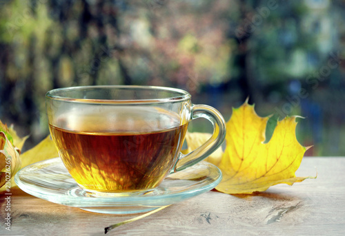 Foto op Aluminium Thee Cup of tea and yellow leaves on a wooden table. Cup with hot tea on wood table over autumn background. autumn background