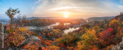 amazing panoramic view of blue foggy river and colorful forest on sunrise. autumn landscape