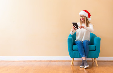 Fototapeta Yong woman with santa hat using her tablet in a chair
