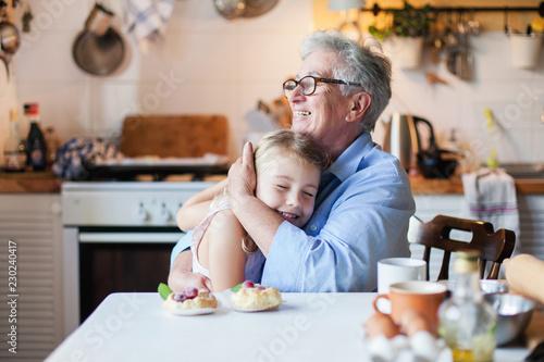 Fototapeta Happy grandmother is hugging granddaughter in cozy home kitchen