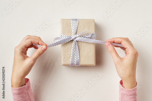 Fotografie, Tablou woman's hands untie bow on gift box on white background, top view