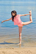 The girl in pink clothes posing against the background of water