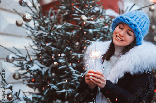 christmas portrait of happy woman with burning firelight walking outdoor in snow Wallpaper Mural