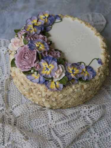 Napoleon cake with vanilla cream, decorated with buttercream flowers - roses and pansies. Vintage style. Gray background, lace napkin. Copy space, close up