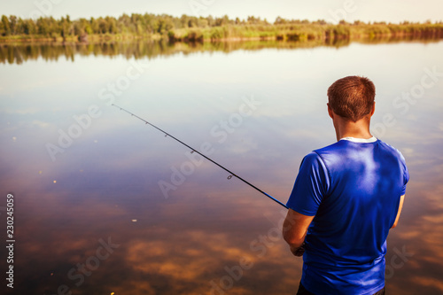 Young man fishing on river bank. Fisherman enjoying hobby. Spinning