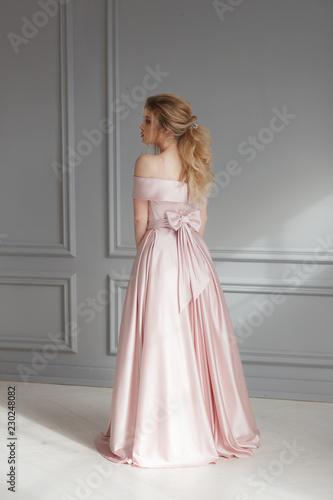 Valokuvatapetti Beautiful blonde woman in beige powdery silk wedding dress posing in studio room