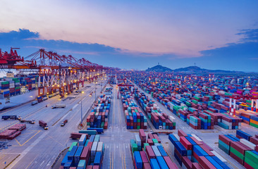Container ship in export and import business and logistics. Shipping cargo to harbor by crane. Water transport International. Aerial view
