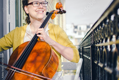 Canvas Female classical musician smiling and playing cello on the balcony
