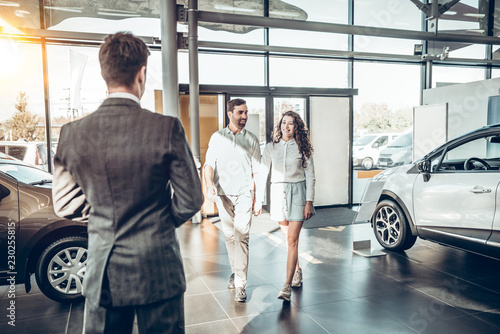 Fotografía young family comes into Car dealership to choose the car to buy it